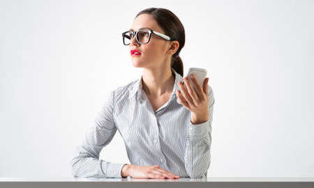 Smiling young woman sits at desk and dreamy looking upward. Portrait of beautiful girl in glasses with bright red lips on white wall background. Human resource and career development concept. 免版税图像