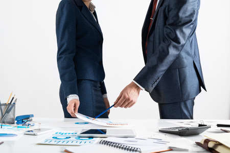 Businessman and businesswoman stand near desk with financial annual report. Business people meeting in conference room. Business idea presentation and analysis. People communication and discussion