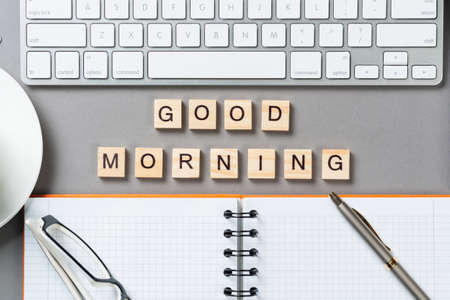 Good morning message with letters on wooden cubes. Still life of workspace with supplies. Flat lay grey surface with computer keyboard and spiral notebook. Morning greeting phrase and motivation. Imagens