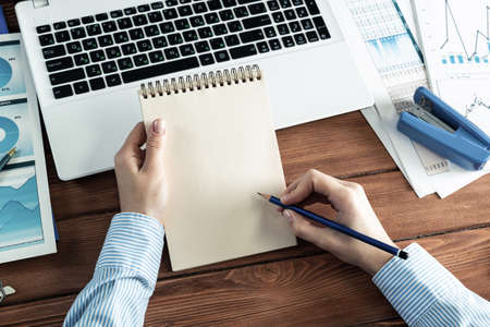 close-up, female hands with notebook and pencil. Business woman working at the table in the office