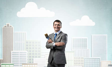 Confident and creative businessman painter standing with arms folded. Happy handsome man in business suit and tie holding paintbrush on background cityscape illustration. Creativity in business. 版權商用圖片