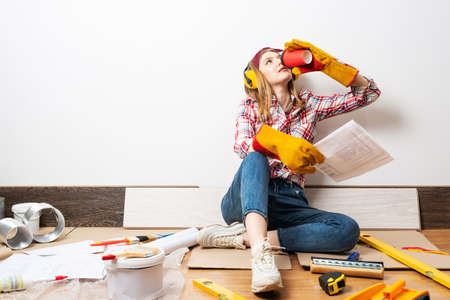 Happy girl in protective headphones and gloves relaxing on floor with coffee. Home remodeling after moving. Young woman wearing checkered shirt and jeans