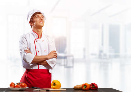 Young male chef standing with folded arms near cooking table with vegetables. Handsome chef in white hat and red apron on light room blurred background. Professional cooking classes advertising.