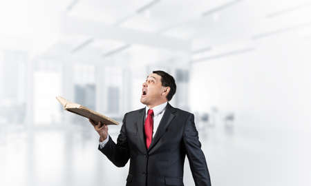 Surprised businessman holding open book and looking up. Startled adult man in business suit and tie standing in blurred office interior. Education and knowledges. New and actual information concept