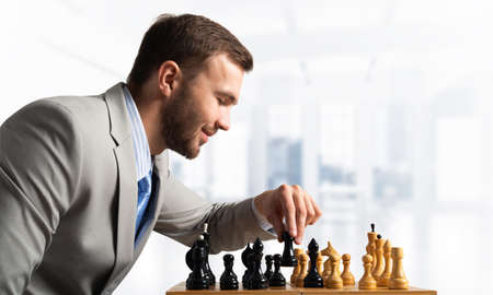 Concentrated businessman playing chess game. Successful management and leadership concept. Confident young man in business suit sitting at desk with chess. Operative tactics and strategy planning