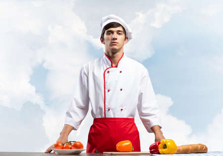 Young male chef standing near cooking table with vegetables. Handsome chef in white hat and red apron on blue sky background. Cooking classes advertising. Restaurant food preparation concept