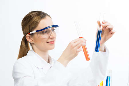 Clinic laboratory analysis and testing. Young woman in protective goggles holding test tube with color liquid. Laboratory assistant comparing samples in test tubes. Biochemistry or chemical research.