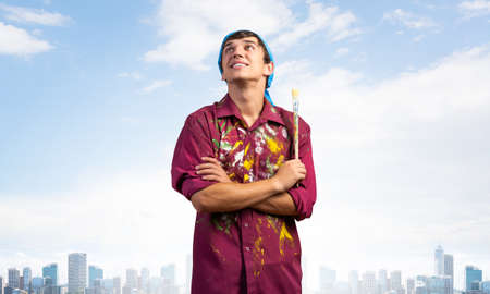 Pensive painter artist standing with folded arms on modern cityscape background. Portrait of young man looking up dreamily. Artistic occupation and creative profession. Art school student posing.