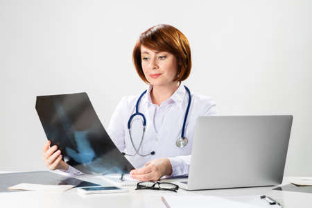 Beautiful doctor looking at x-ray scan in office. Physician in white coat with stethoscope sitting at desk with laptop. Professional medical diagnosis and treatment in clinic. Medical check up service