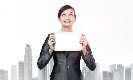 Businesswoman holding tablet computer with blank screen. Smiling woman in business suit show tablet PC and looking upward. Corporate businessperson on downtown background. Digital technology layout