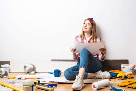 Beautiful woman sitting with paper blueprint in hand. Home remodeling and house interior redesign. Construction tools and materials lying on floor.