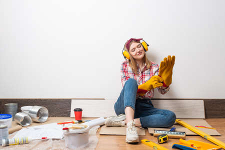 Happy woman in protective headphones and gloves sitting on floor. Home remodeling after moving concept. Construction tools and materials for building.
