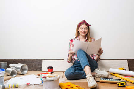 Happy pretty girl sitting on floor with paper blueprint. Home remodeling and house interior redesign. Young woman studying renovation project of flat.
