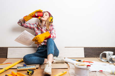 Happy girl in protective headphones and gloves relaxing on floor with coffee. Young woman wearing checkered shirt and jeans Stock fotó