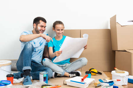 Happy couple sitting on floor with construction blueprint. Home remodeling and house interior redesign. Construction tools and materials lying on floor. Young family studies renovation project of flat