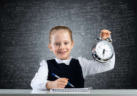 Smiling little girl holding alarm clock. Time to study and back to school concept. Happy schoolgirl sitting at desk with notebook and pen in hand. Time management. Research and education in school.
