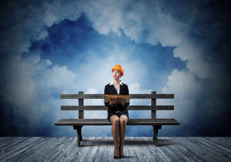 Beautiful woman architect sitting on wooden bench. Young technician specialist in orange safety helmet holding open book in hands on cloudy night sky background. Engineering and development company