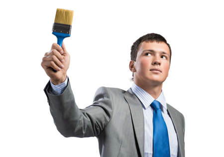 Confident and creative businessman painter holding paintbrush in hand. Portrait of handsome young man in business suit and tie isolated on white background. Ambitions and creativity in business. Stok Fotoğraf