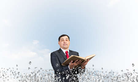 Happy businessman holding open old book. Smiling man in suit standing on city background with flying around various letters. Bookkeeper holding accountant book. Business accounting and consulting Stok Fotoğraf