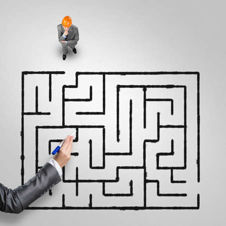 Top view of puzzled businessman in helmet looking at drawn maze on floor Stok Fotoğraf