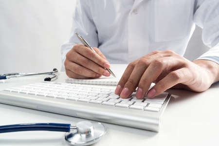 Doctor typing on wireless computer keyboard in office. Physician in white medical gown works with computer at desk. Professional diagnosis and treatment in modern hospital. Professional healthcare