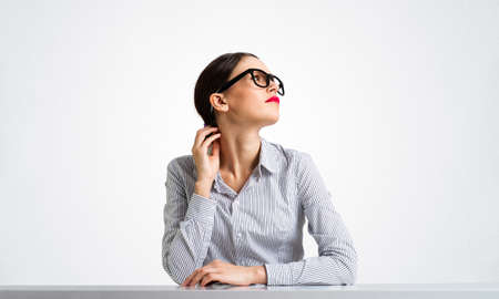 Confident businesswoman sits at desk and looking away. Young student has serious facial expression. Portrait of beautiful girl in glasses. Human resource and career development concept with copy space