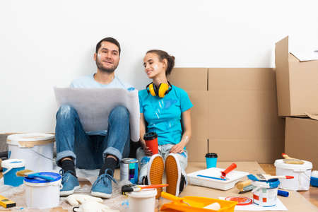 Young man and woman together planning their home renovation. Cardboard boxes, painting tools and materials on floor. House remodeling and interior renovation. People looking at blueprint at home.