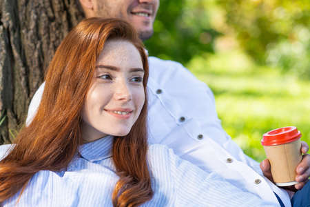 Young couple relaxing under tree in summer park on sunny day. Happy couple in love spend time outdoors together. Handsome man and pretty redhead girl enjoying each other. Romantic relationships.