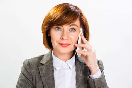 Close up redhead businesswoman talking on smartphone in office. Concentrated lady at desk on white background. Corporate woman in suit at her workplace. Business communication and consultation.