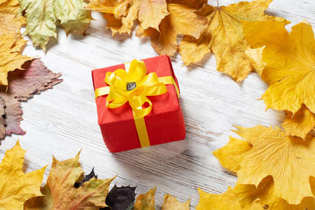 Bright autumn composition with gift box and yellow maple leaves. Holiday present decorated yellow ribbon bow lies on vintage wooden desk. Happy thanksgiving congratulation. Autumn sale advertising. Stok Fotoğraf