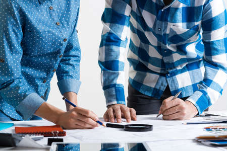 Man writing with pen on technical drawing. Creative team of designers together working with construction blueprint. Thorough study and approval of design project. Architecture studio concept. Stok Fotoğraf