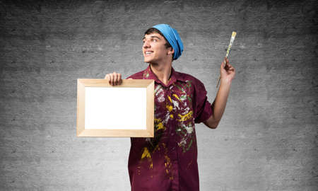 Young handsome painter artist holding paintbrush and blank canvas in frame. Portrait of happy painter on gray wall background. Creative hobby and artistic occupation. Art school advertising.