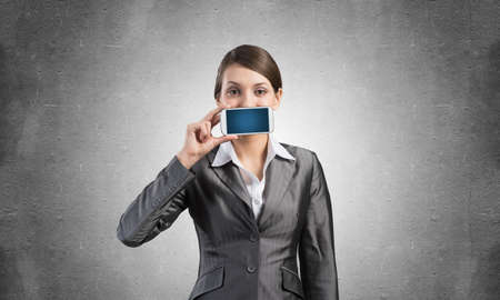 Portrait of young woman covering her mouth with smartphone. Businesswoman showing mobile phone with blank screen. Corporate businessperson on grey wall background. Mobile communication layout. Stok Fotoğraf