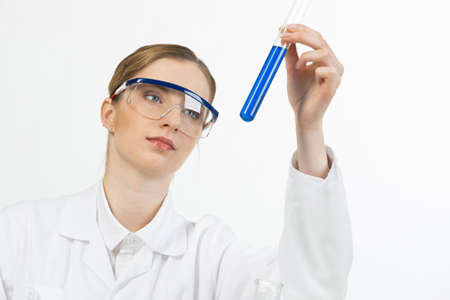 Beautiful young woman scientist in protective goggles looking at test tube with liquid in hand. Laboratory assistant conducts chemical experiment. Pharmaceutical research and medicaments testing.