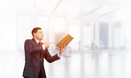 Senior businessman finger pointing into open book. Portrait of adult man in business suit and tie standing in blurred office interior. Manager holding big handbook. Professional reference information.