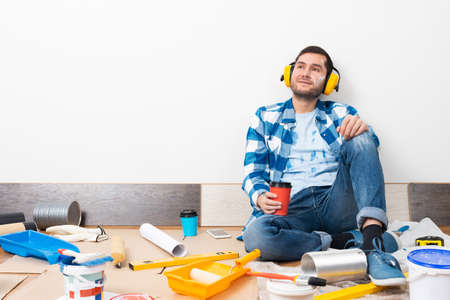 Happy boy in protective headphones sitting on floor. Home remodeling after moving. Construction tools and materials for building. Young man in casual clothes holding coffee cup and paint roller
