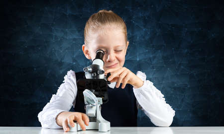 Little girl scientist looking through microscope in classroom at biology lesson. Research and discovery. Formal education in modern school. Schoolgirl in schoolwear making experiment in class.