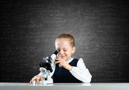 Little girl scientist looking through microscope in classroom at lesson. Research and discovery. Formal education in modern school. Schoolgirl in schoolwear making experiment in class with chalkboard.