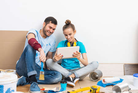 Happy couple watching something funny on tablet computer while sitting on floor. Painting tools and materials for home remodeling and interior redesign. Young family renovating their home after moving Banque d'images