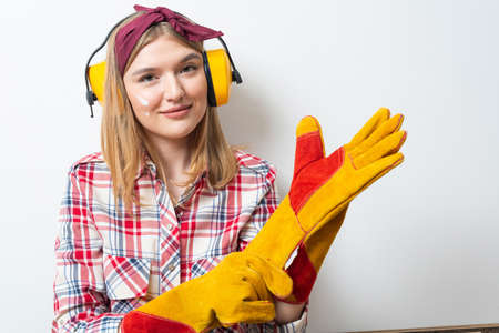 Attractive girl in protective headphones and gloves posing on white wall background. Home remodeling after moving concept. Young woman in checkered shirt and jeans planning to redesign her home.