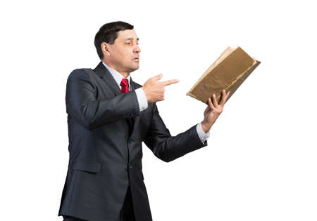 Senior businessman finger pointing into open book. Portrait of adult man in business suit and tie standing on white background. Manager holding big handbook. Professional reference information.