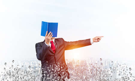 Businessman covered his face with organizer and finger pointing side. Man in business suit and tie standing on city background with flying various letters. Education and professional knowledges.