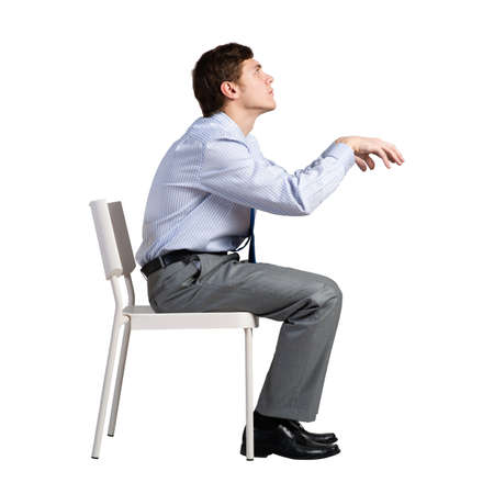 businessman sits on a chair, plays an imaginary piano