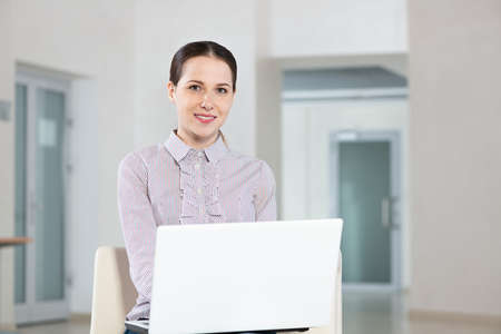 Attractive young woman works with a laptop