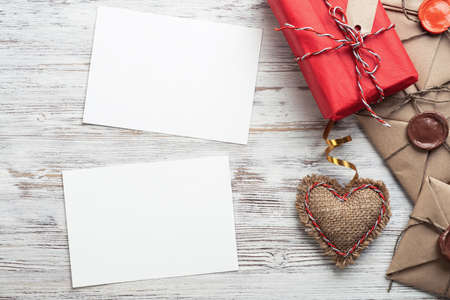 Flat lay cute composition with handmade fabric heart. White paper and retro mail envelopes on wooden table. Happy birthday or anniversary congratulation. Romantic message template with copy space