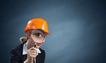 Professional appraiser looking through magnifying glass. Woman civil engineer in safety helmet checking with magnifier on wall background. Technical condition assessment, consultancy and expertise