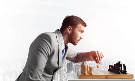 Concentrated businessman playing chess game. Successful management and leadership concept. Confident young man in business suit sitting at desk with chess. Operative tactics and strategy planning Foto de archivo