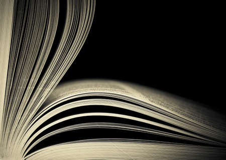 Close-up of opened book pages against black background. Space for text. Shallow DOF. Stock Photo