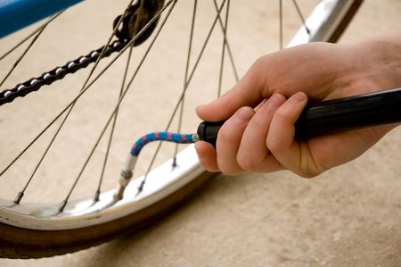 Inflating the tire of a b�cycle. Focus is on the hand.