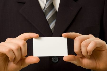 Businessman holding blank business card with both hands photo